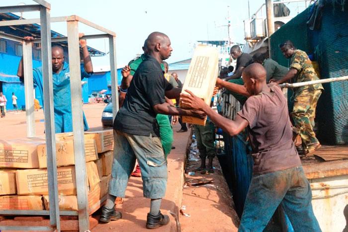 工人由渔船搬下一箱箱的物品。