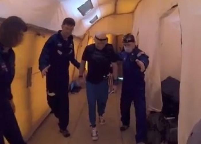 斯科特.凯利(右二)在白色长形帐篷的长廊上步行。