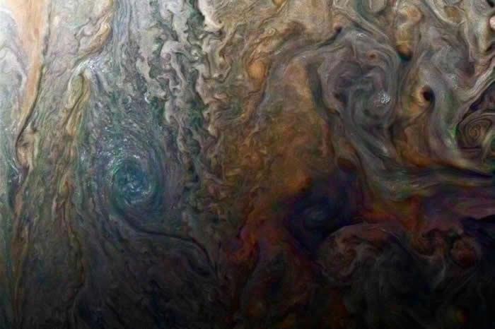 这幅朱诺号色彩强化的影像,显现出木星上神秘的黑斑。 PHOTOGRAPH BY NASA