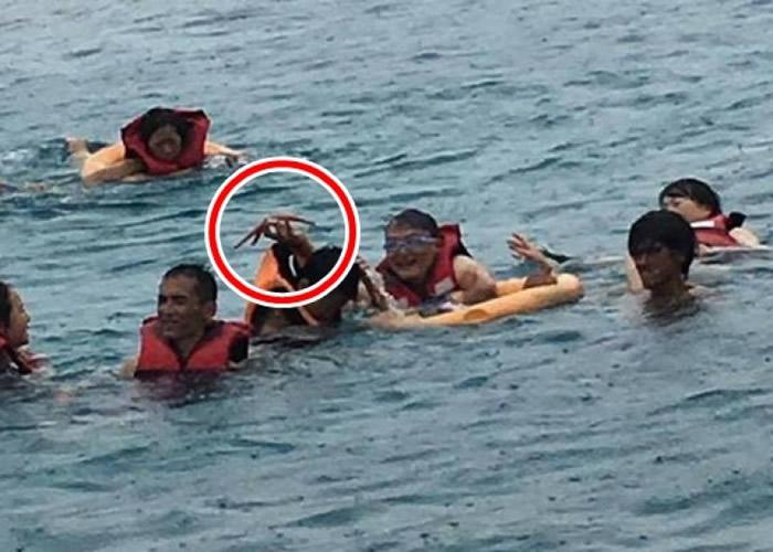 旅客到海中抓海星拍照。