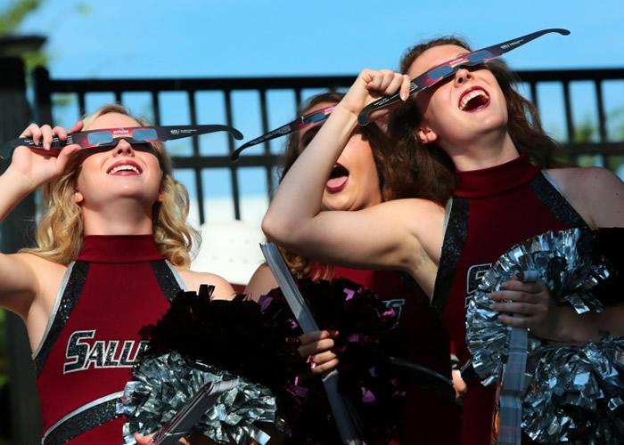 大学啦啦队少女暂停排练,在运动场上观看日食。