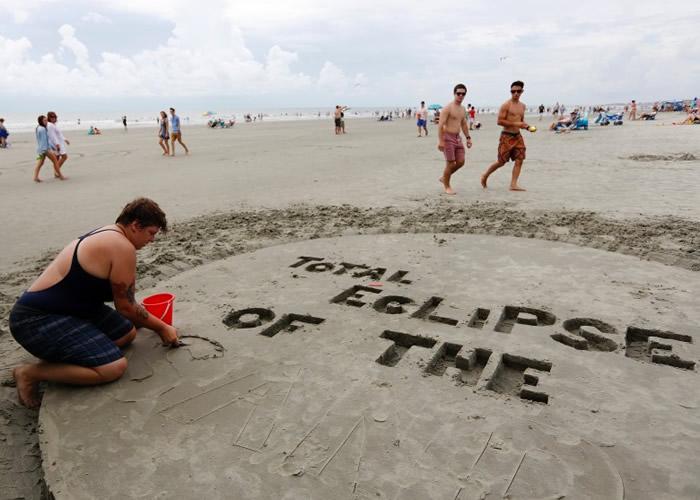 沙滩客用心堆砌字样迎接日食。
