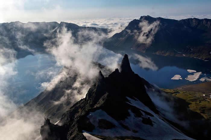 从朝鲜两江道(Ryanggang Provnice)空拍白云笼罩的白头山。 PHOTOGRAPH BY DAVID GUTTENFELDER, AP