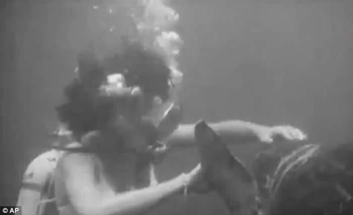 一名比基尼女郎正与海龟互动交流。