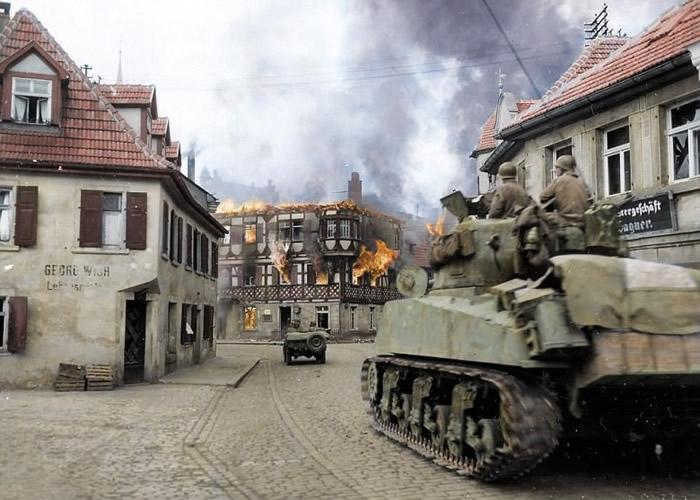 美国陆军装甲师士兵驾驶战车进入小镇。