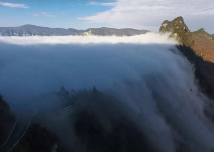 """云雾自山体一侧向山谷""""俯冲""""而下,如天河倾泻,气势磅礴。"""