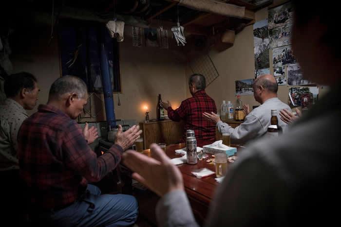 分配猎物后,小国町的猎人聚在佐藤队长的家里,开始仪式。远藤先生是群体中备受敬重的又鬼猎人,他以一颗熊的心脏与一瓶清酒来主持祈祷。 PHOTOGRAPH BY J