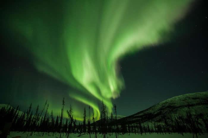 来自太阳的带电粒子与地球大气层中的气体相互作用,产生壮丽的极光,就像闪闪发光的光帘,妆点了阿拉斯加的夜空。 PHOTOGRAPH BY MARK THIESSE