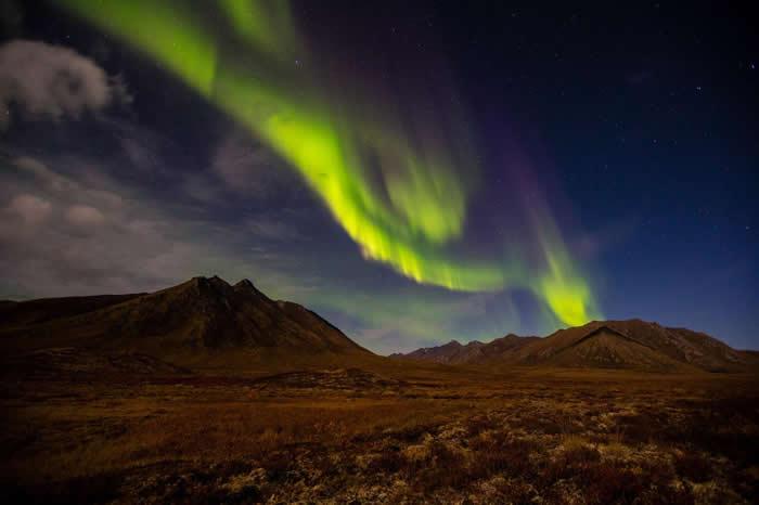 在加拿大育空(Yukon)地区,缕带状的极光萦绕在夜空之中。来自太阳的粒子沿着地球的磁力线往两极流动,因此在高纬度地区最容易看到极光。 PHOTOGRPAH B