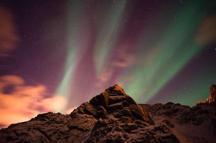 在挪威西奥伦群岛(Vesteralen Islands)上的这座山峰,耸立直入满布极光的天空。 PHOTOGRAPH BY SERGIO PITAMITZ, N