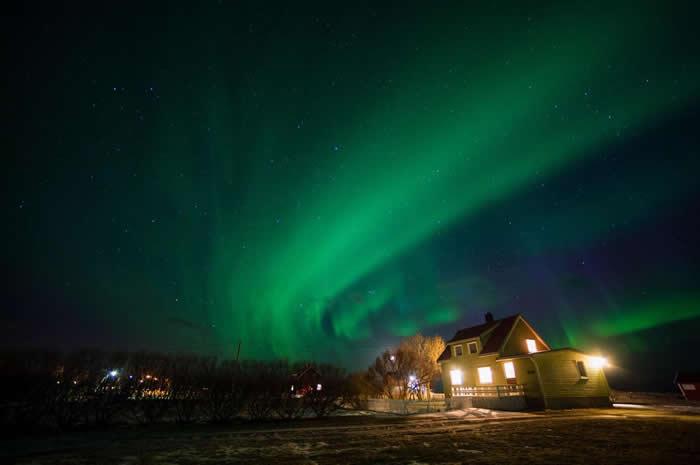 挪威诺尔兰郡(Nordland)的这座房子,沐浴在流淌而过的极光之中。 PHOTOGRAPH BY SERGIO PITAMITZ, NATIONAL GEOG