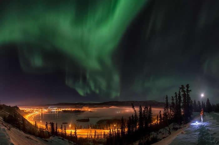 在加拿大育空地区,有名男子正在观看白马市(Whitehorse)上方壮丽的北极光。 PHOTOGRAPH BY PETER MATHER, NATIONAL G