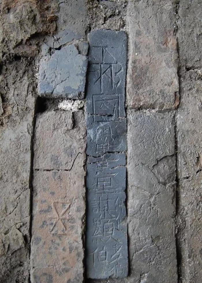 """墓地门墙砌砖刻有""""下邳国县建忠里谋显伯仲伯孝伯""""。"""