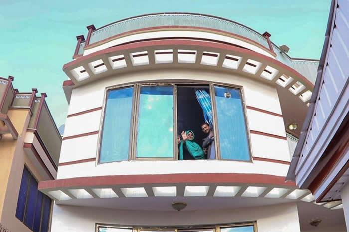 夏帕特.古拉从新家的窗户向外挥手。阿富汗政府为她的家庭支付房租与生活费。 COURTESY ADMINISTRATIVE OFFICE OF THE PRESI