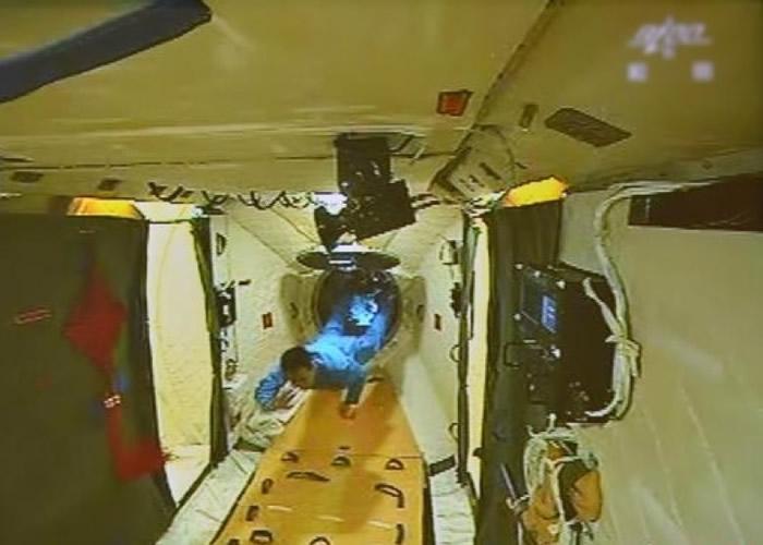 图为早前聂海胜顺利开启并进入天宫一号舱门。(资料图片)