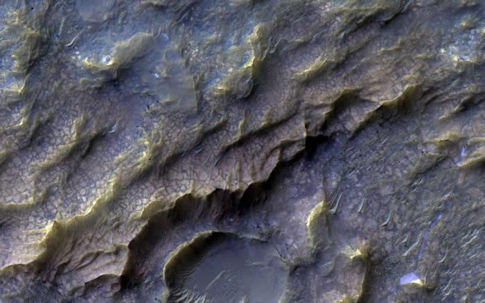 影像中浅红色的鳞状结构,是在很久以前由流水形塑的火星岩盘,形成含有黏土的岩石。目前我们还不清楚火星上的岩石和流水,是如何产生交互作用的。 PHOTOGRAPH