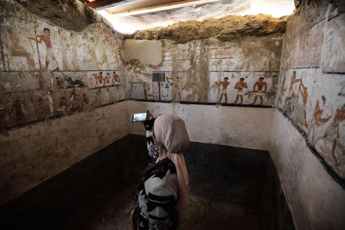 女子在古墓中拍照,墓室座落在开罗的吉萨平原上,属于古王国(Old Kingdom)时期一名女祭司,墓中装饰着保存良好的珍稀壁画。 PHOTOGRAPH BY M