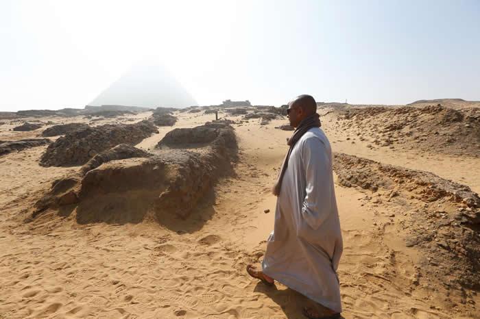 男子走在开罗郊区吉萨平原新发现的古墓附近,这里有三座古代金字塔。 PHOTOGRAPH BY AMR ABDALLAH DALSH, REUTERS