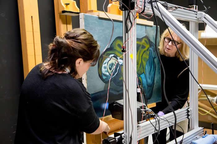 西北大学的艾米琳.普叶(左)与安大略美术馆的珊卓.韦布斯特库克架设了X射线萤光仪来扫描毕卡索的画作〈蹲坐的行乞者〉。 PHOTOGRAPH COURTESY A