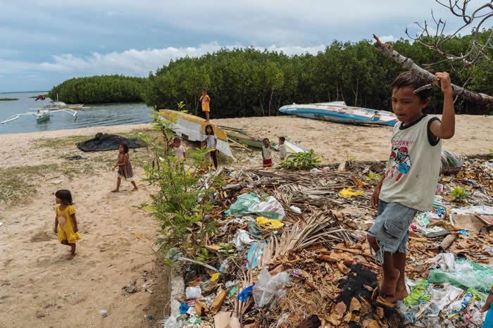 孩童在菲律宾保和岛的一个垃圾堆旁边玩耍。在大潮或下雨的时候,这里的垃圾会溢流到海里。菲律宾是全球海洋生物多样性的中心,但在污染海洋方面,也仅次于中国与印尼,全球