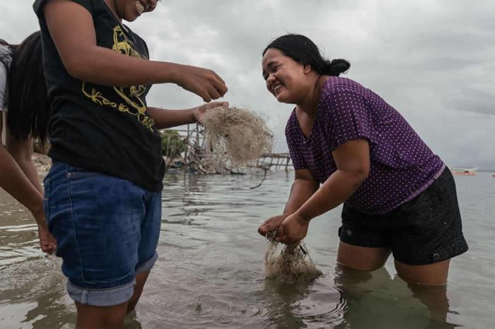 菲律宾妇女正在清洁要卖到国外再造的废弃渔网。 PHOTOGRAPH BY HANNAH REYES MORALES, NATIONAL GEOGRAPHIC