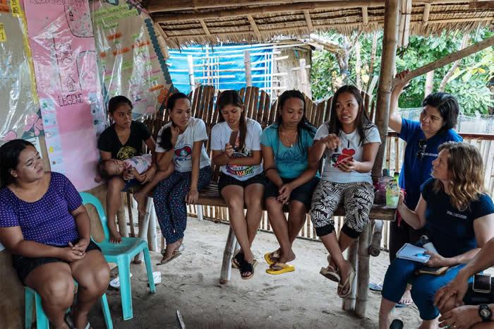 社区居民与国家地理探险家海瑟.寇德威(右)见面讨论如何由垃圾中获利。 PHOTOGRAPH BY HANNAH REYES MORALES, NATIONAL