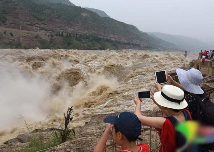 众多游客到壶口瀑布观赏拍照。