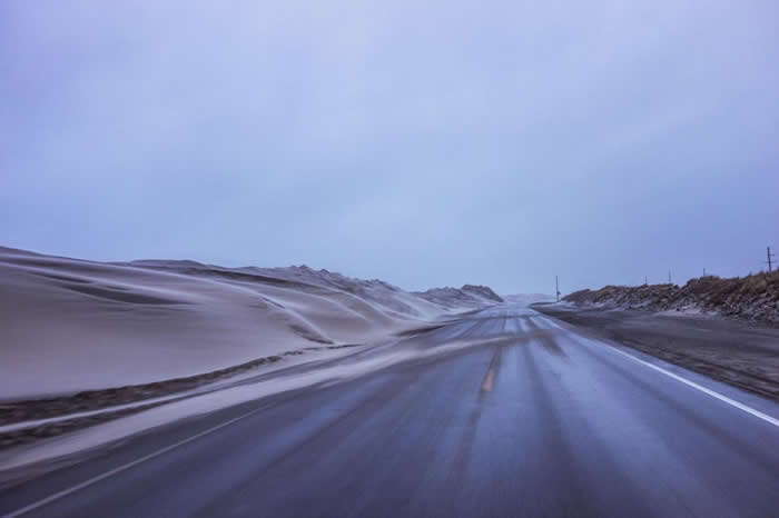 被风吹袭的沙子掩埋了北卡罗来纳州的12号公路,造成道路封闭。它的保养和修理费用变成纳税人越来越沉重的负担。 PHOTOGRAPH BY JOHN TULLY