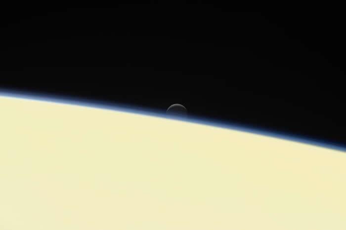 美国航太总署的卡西尼号太空船在2017年9月15日冲入土星自毁,这张影像是卡西尼号所拍摄的告别作之一,可以看到冰冷的土卫二沉没在土星后方。 PHOTOGRAPH
