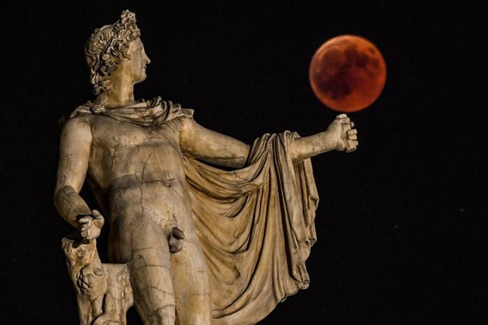 血月恍如成为希腊雅典的阿波罗神像的玩具。