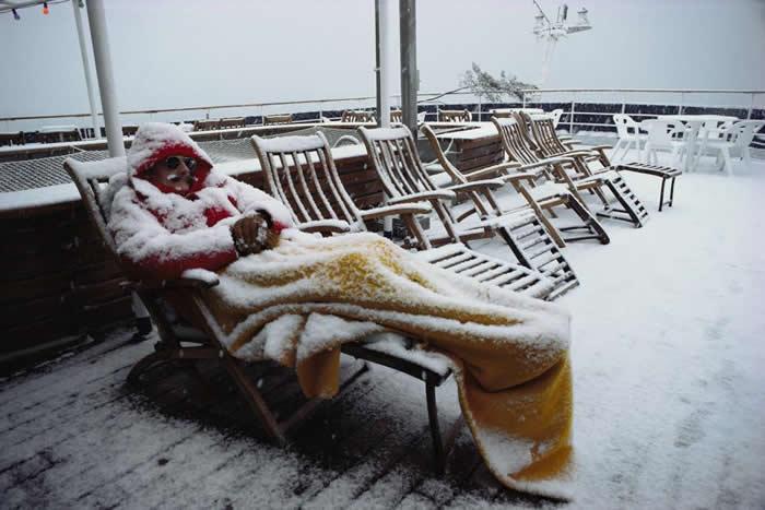 阿曼森海(Amundsen Sea)附近,有一位认真的南极游客,在下雪时还睡在甲板椅上。 PHOTOGRAPH BY COLIN MONTEATH, MINDE