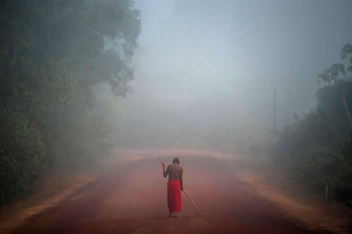 巴西阿马帕州(Amapa),怀亚皮原住民保留区的马尼利亚(Manilha)村里,走在雾中的部落头目札科.怀亚皮(Tzako Waiapi)。在亚马逊地区,尚未接