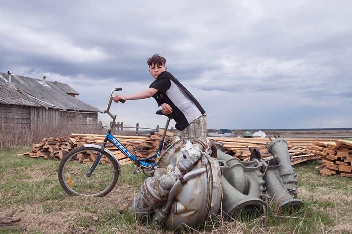 13岁的安东(Anton)站在俄罗斯北方道嘉屈莱村(Dolgoshchel'ye)的一块火箭零件旁边。北极圈下方约有10个聚落的居民会去捡拾太空垃圾,这个村子就