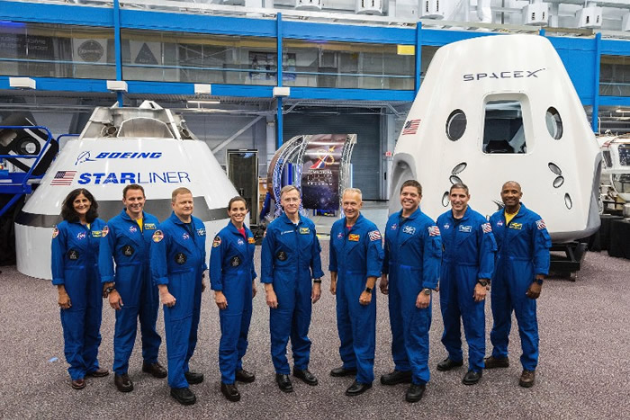 获挑选的宇航员与CST-100 Starliner(左后)及龙号(右后)太空船合照。