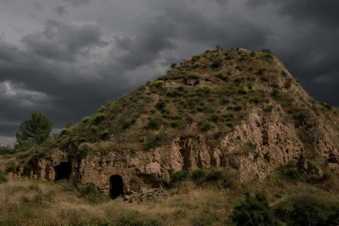 西班牙南部贝纳卢阿村(Benalúa)的一间洞穴屋,入口上方的天色暗了下来。 PHOTOGRAPH BY TAMARA MERINO