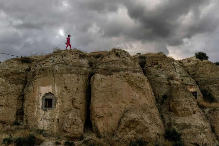 住在瓜地什的12岁女孩茱蒂丝(Judith)从一间洞穴屋的上方走过。数百年以来,这个地区一直是地下居民的住所。 PHOTOGRAPH BY TAMARA MER