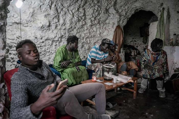 塞内加尔移民坐在山坡高处的一个洞穴内。虽然萨克罗蒙特的洞穴一向被认为是罗姆人的家,但这里的居民实际上来自各地。 HOTOGRAPH BY TAMARA MERI