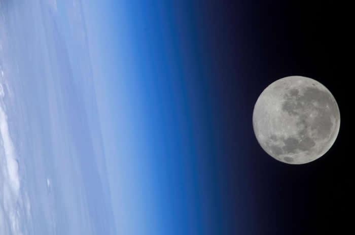从国际太空站(International Space Station)看到的满月好像掠过了地球的大气层。 PHOTOGRAPHY BY NASA, INTERN
