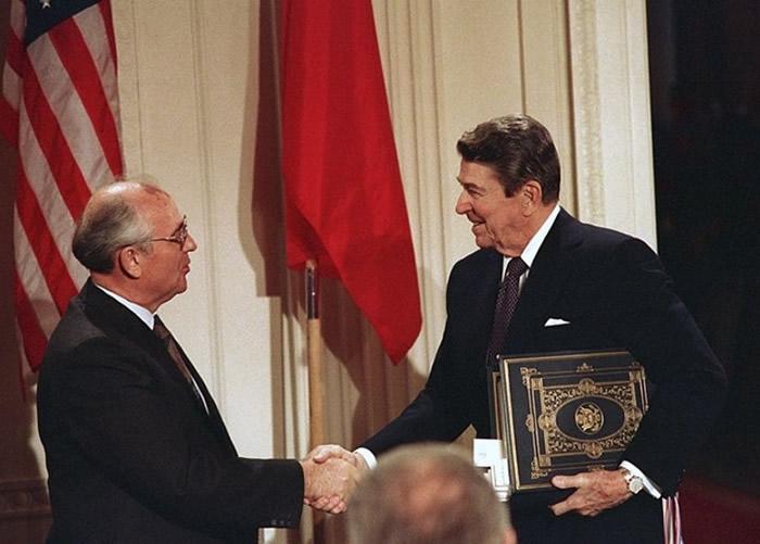 前苏联领袖戈尔巴乔夫(左)与美国总统里根(右)签署《中程导弹条约》。