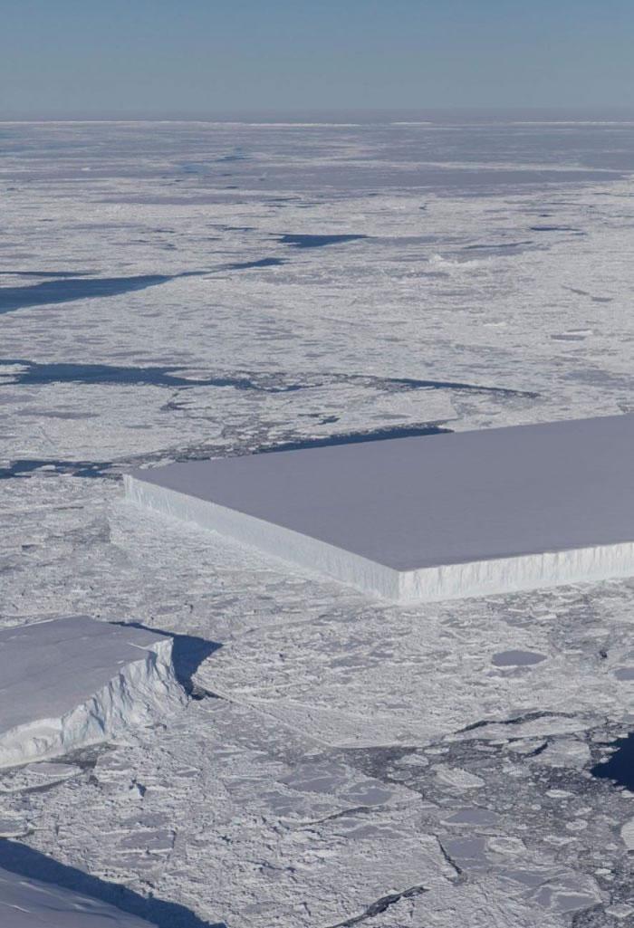 执行冰桥行动的飞机拍摄到的影像:照片右方可以看到一个平板状的冰山漂浮在拉森C冰棚外的海冰之间。这个冰山锐利的角度和平坦的表面显示它可能最近才刚从冰棚崩裂下来。