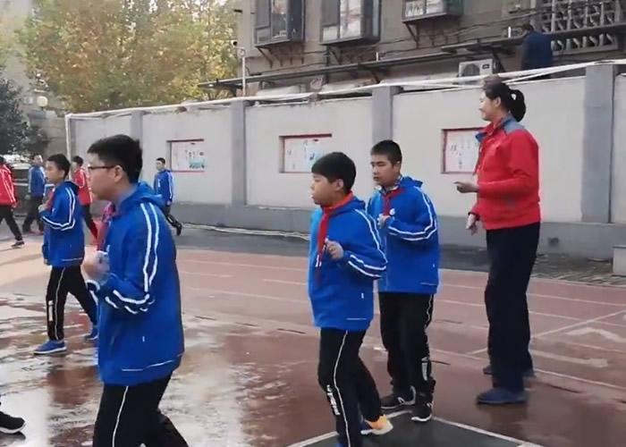 张子宇(右)像巨人般站在同学身旁做早操。