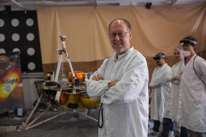 在洞察号着陆前的几个星期,洞察号的主要负责人布鲁斯.巴纳特站在模拟着陆过程的复制模型旁。 PHOTOGRAPH BY CASSANDRA KLOS