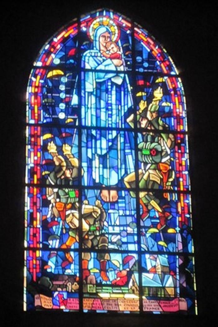 教堂彩绘玻璃描绘伞兵降落于圣母玛莉亚面前,其中一人便是约翰。