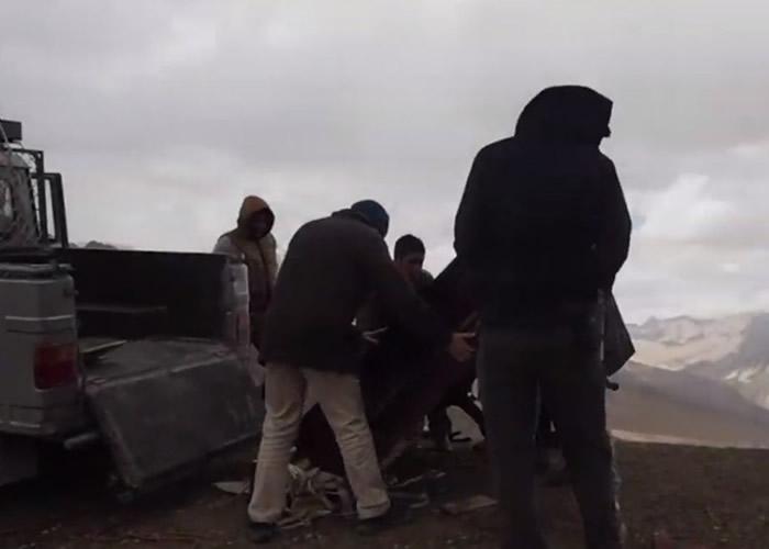 工作人员协助把钢琴运上高地。