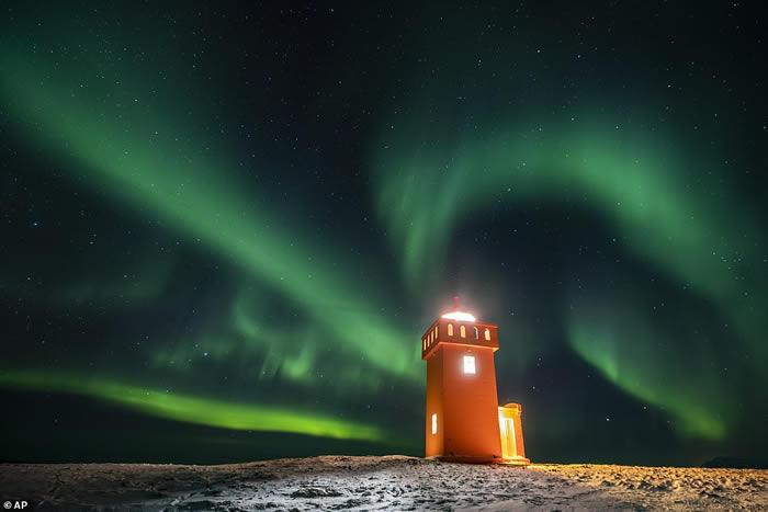 冰岛Grundarfjorour村灯塔上方天空中的北极光。极光是由来自太阳的高能带电粒子与地球大气层中的气体分子之间的相互作用引起的。
