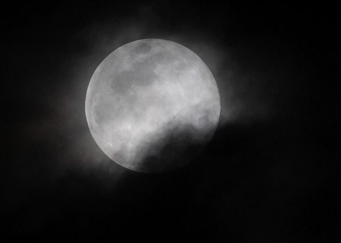 美国看到的圆月被薄雾遮掩。