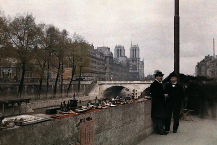 1920年代,两个男人站在塞纳-马恩省河畔待价而沽的小饰品旁边,背后就是巴黎圣母院。 PHOTOGRAPH BY JULES GERVAIS COURTELLE