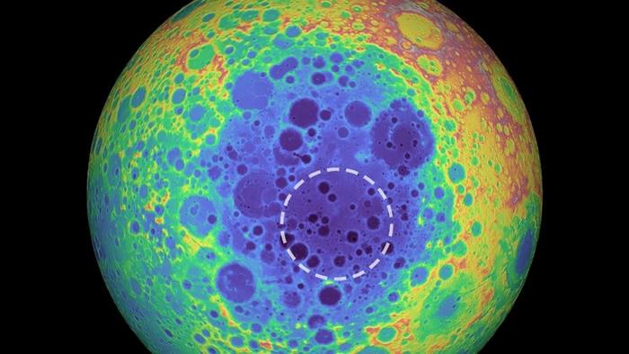 这张伪色影像是月球背面的地形图,较暖的色调显示海拔较高的区域,而较冷的色调则显示海拔较低的区域。 虚线圆圈表示南极-艾托肯盆地下方的质量异常区域。 IMAGE