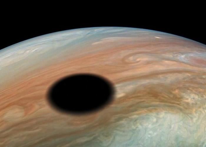 """朱诺号探测器低飞木星拍下令人叹为观止的日偏食 """"木卫一""""掠过木星表面"""