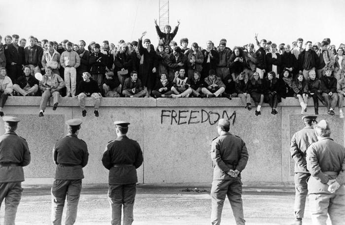 在柏林围墙倒下的1989年11月,西德民众在东德卫兵面前爬上了这道冷战藩篱。 PHOTOGRAPH BY HESSE, ULLSTEIN BILD/GETTY